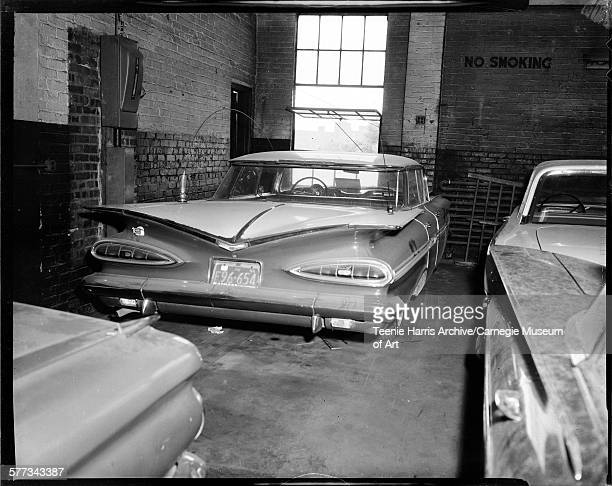 Rear view of two toned Chevrolet car with PA 1958 license plate F96654 parked in garage with three other cars Pittsburgh Pennsylvania 1962