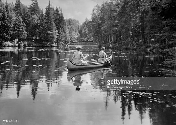 Rear view of two women paddling the tranquil waters of an Adirondack Mountain lake in the late 1930s.