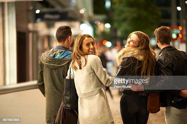 Rear view of two young couples strolling arm in arm along street at night, London, UK