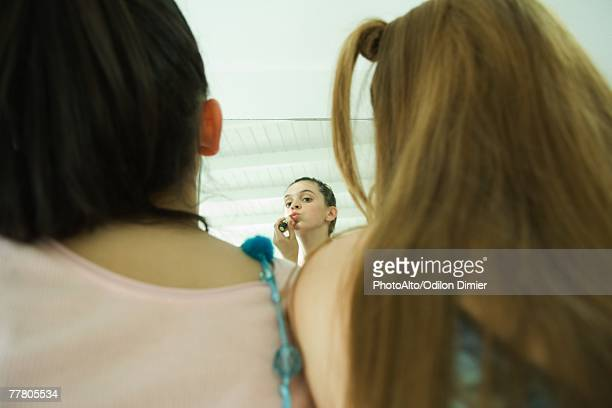Rear view of two young friends, one looking at self in mirror, applying lipstick