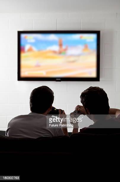 Rear view of two young man on a sofa playing XBox 360 video games on a wall-mounted television, taken on July 9, 2013.