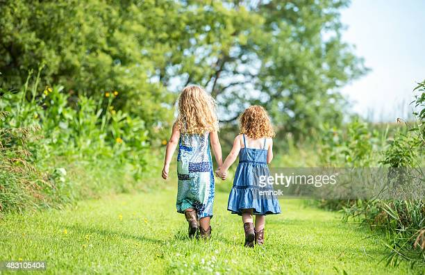 rear view of two young sisters walking holding hands - denim dress stock photos and pictures
