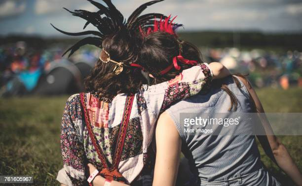 Rear view of two young women at a summer music festival wearing feather headdresses, arm around shoulder.