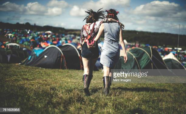 Rear view of two young women at a summer music festival wearing feather headdresses, walking arm in arm towards tents.