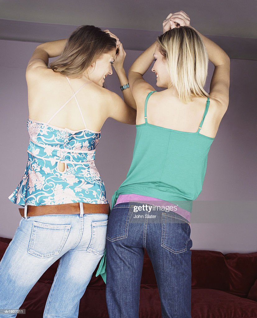 Rear View of Two Young Women Dancing Side by Side, in Unison : Stock Photo