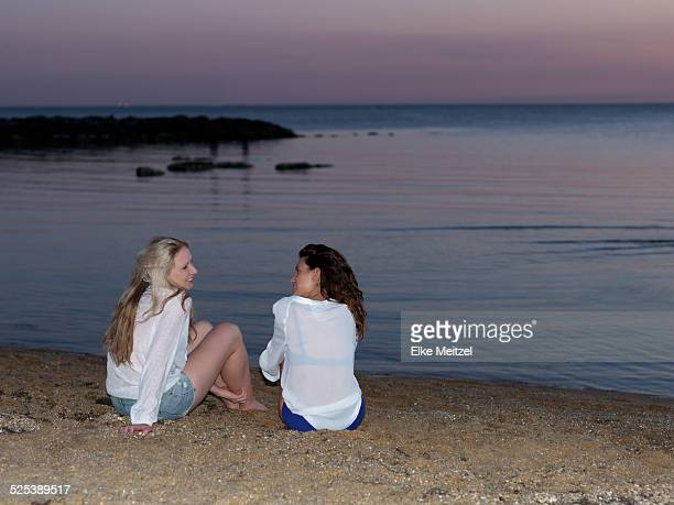Rear view of two young women friends sitting chatting on beach at sunset, Williamstown, Melbourne, Australia