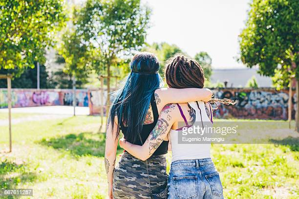 Rear view of two young women in urban park