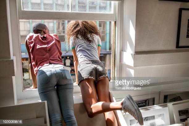 rear view of two young women leaning out of window - hot pants stock-fotos und bilder