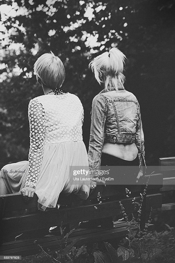 Rear View Of Two Young Women Sitting On Benchs Back : Foto stock