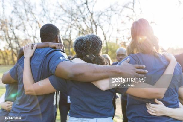 achteraanzicht van de verenigde groep van vrijwilligers - liefdadigheidswerk stockfoto's en -beelden