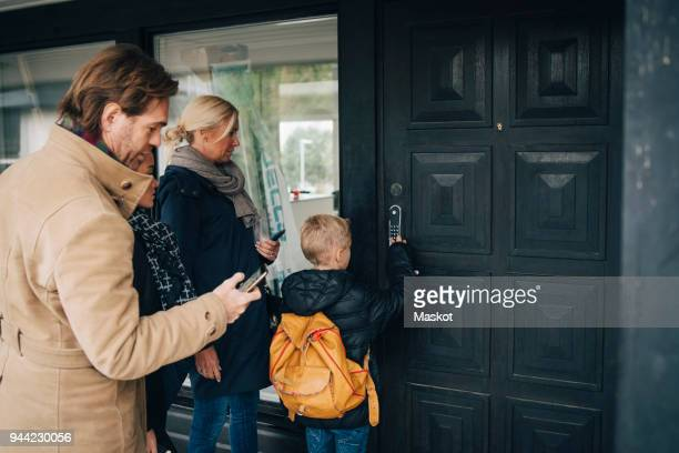 Rear view of unlocking combination lock on house door by family