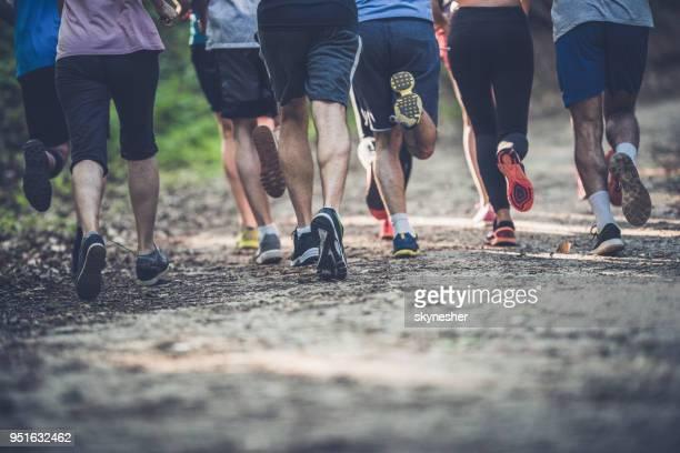 achteraanzicht van onherkenbaar atleten lopen van een marathon in de natuur. - baanevenement stockfoto's en -beelden