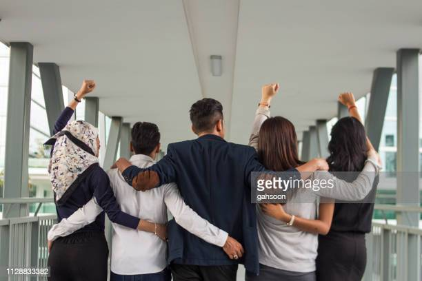 rear view of unrecognizable business team with arms around one another - arm around stock pictures, royalty-free photos & images