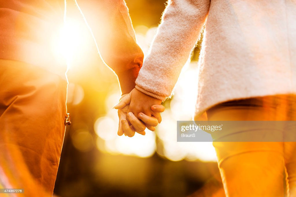 Rear view of unrecognizable couple holding hands at sunset. : Stock Photo