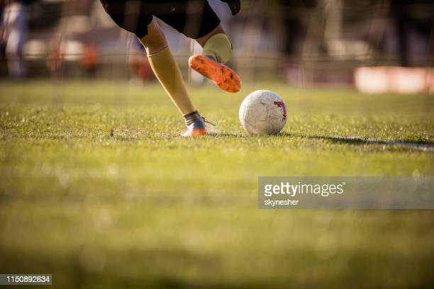 rear view of unrecognizable  soccer goalie kicking the ball. - portiere posizione sportiva foto e immagini stock