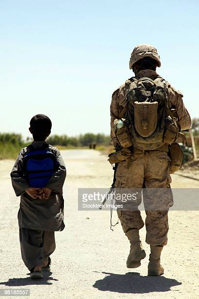 Rear view of U.S. Marine walking through Nawa bazaar with an Afghan boy in Afghanistan.