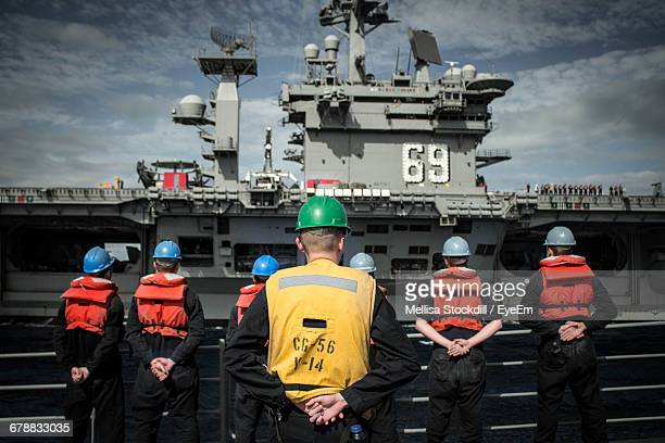 Rear View Of Us Navy Soldiers Standing Against Ship