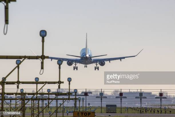 Rear view of various aircraft landing behind the runway lights in Amsterdam Schiphol AMS EHAM International Airport in The Netherlands. The world...