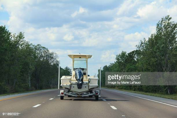 rear view of vehicle towing a boat trailer with fishing boat on highway - towing stock photos and pictures