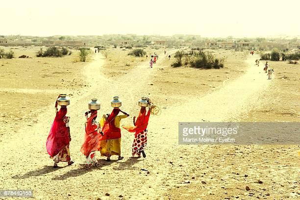 rear view of villages carrying water pots on their heads - village stock pictures, royalty-free photos & images