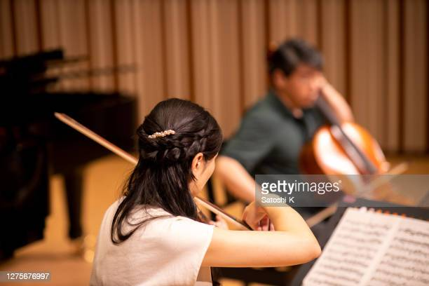 rear view of violinist and cellist playing instruments in concert hall - classical musician stock pictures, royalty-free photos & images