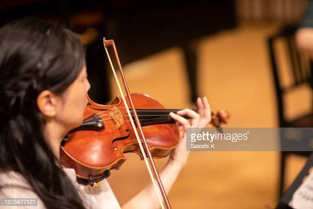 rear view of violinist playing violin at classical concert - classical musician stock pictures, royalty-free photos & images