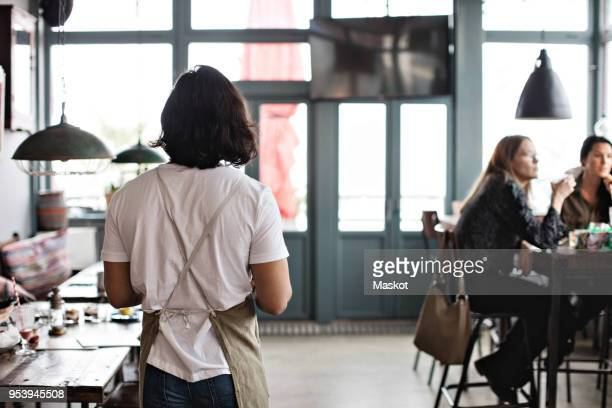 Rear view of waiter walking by female customers at restaurant
