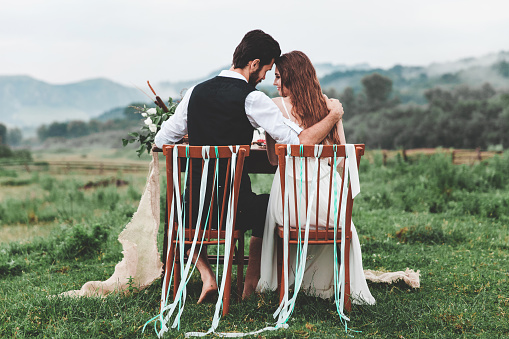Rear View Of Wedding Couple Sitting On Chairs At Farm - gettyimageskorea
