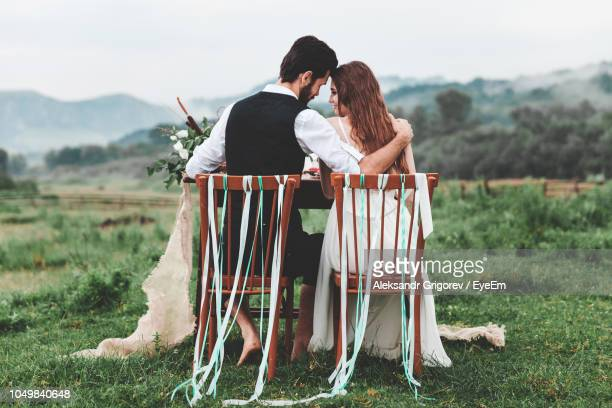 rear view of wedding couple sitting on chairs at farm - trouwen stockfoto's en -beelden