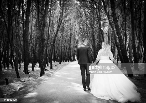rear view of wedding couple walking on road amidst trees - marriage stock pictures, royalty-free photos & images
