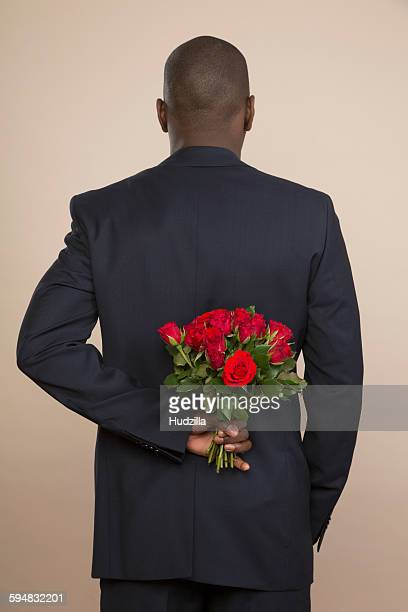 rear view of well-dressed man holding roses against colored background - black rose stock pictures, royalty-free photos & images