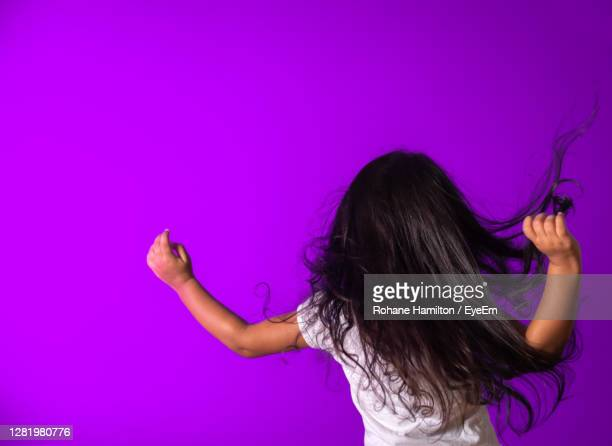 rear view of woman against purple wall - hamiltonmusical stockfoto's en -beelden