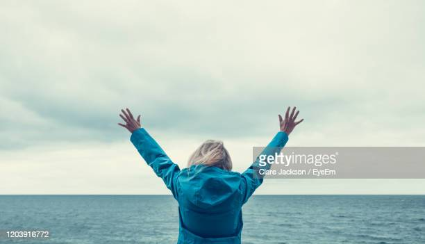 rear view of woman against sea and sky - scenics stock pictures, royalty-free photos & images