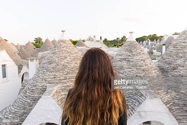 Rear View Of Woman Against Trulli Houses At Alberobello