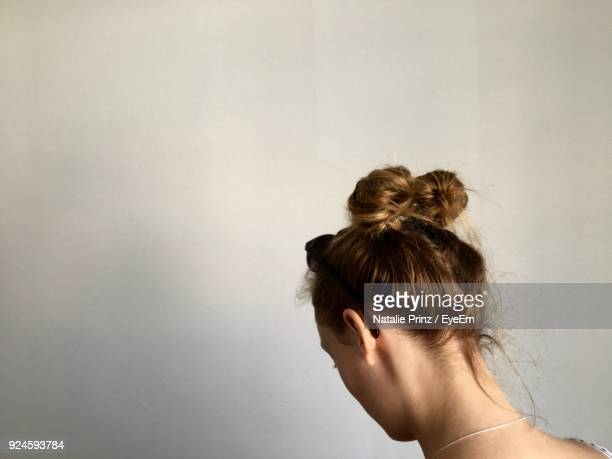 rear view of woman against white wall - up do stock pictures, royalty-free photos & images