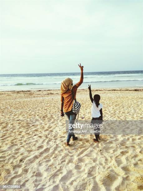 Rear View Of Woman And Girl Gesturing Peace Sign While Standing On Sand At Beach Against Sky