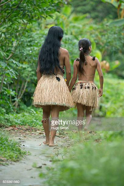 Rear view of woman and girl (8-9) in traditional skirts, Amazon River Basin, Ecuador