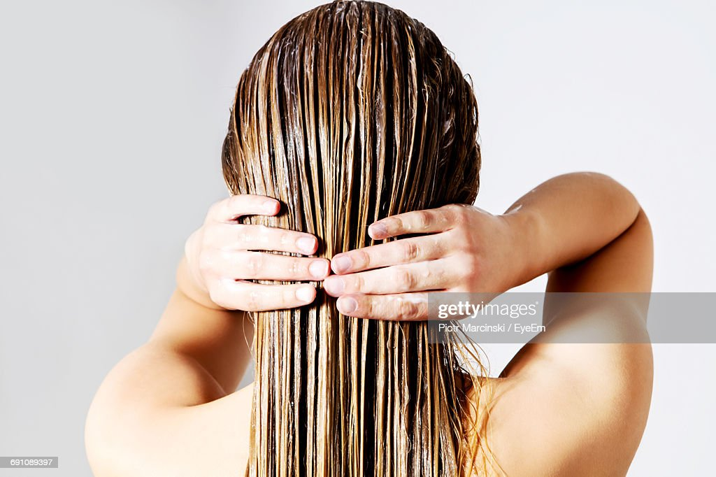 Rear View Of Woman Applying Conditioner On Hair Against White Background : Stock Photo