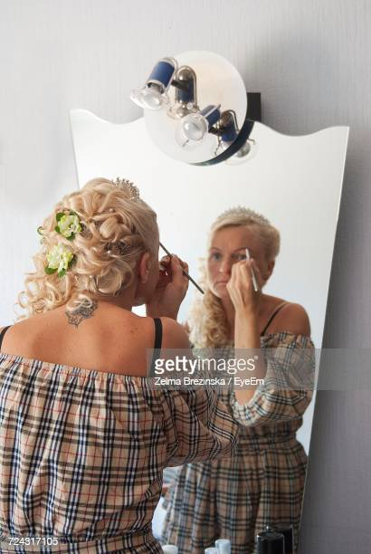 Rear View Of Woman Applying Eye Make-Up While Looking In Mirror Against Wall
