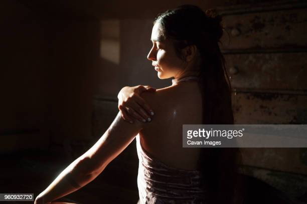 rear view of woman applying oil to body in darkroom at home - aromatherapy oil stock pictures, royalty-free photos & images