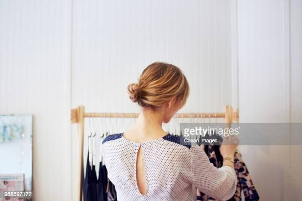 Rear view of woman arranging clothes in rack