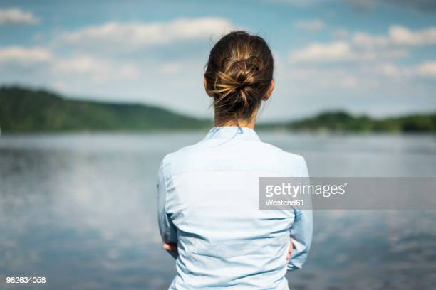 rear view of woman at a lake looking at view - coque cabelo para cima - fotografias e filmes do acervo