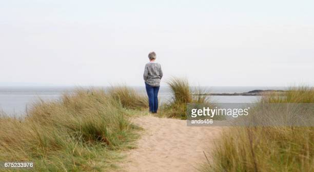 rear view of woman at beach - one senior woman only stock pictures, royalty-free photos & images