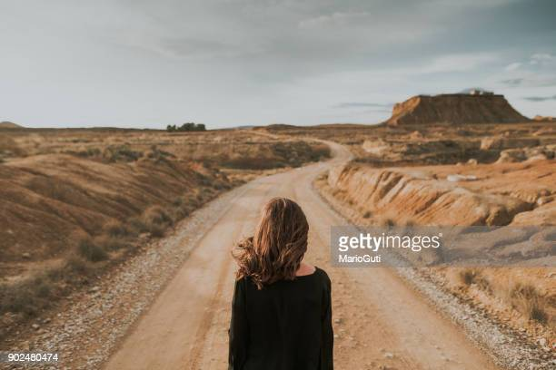 rear view of woman at desert road - arid stock pictures, royalty-free photos & images
