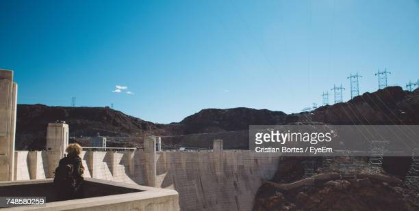 rear view of woman at hoover dam against blue sky - hoover dam stock photos and pictures