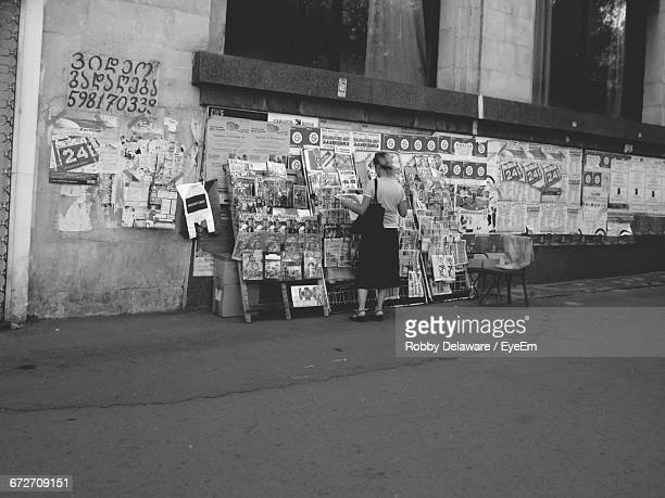 rear view of woman at news stand - news stand stock pictures, royalty-free photos & images