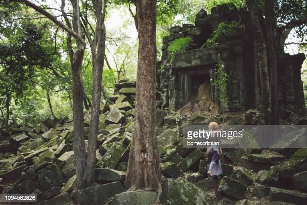 rear view of woman at old ruins in forest - bortes bildbanksfoton och bilder