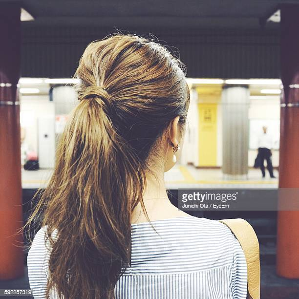 rear view of woman at railroad station - ponytail stock pictures, royalty-free photos & images