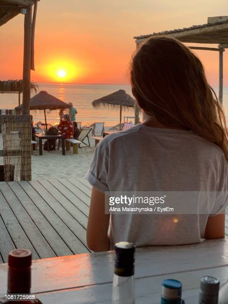 Rear View Of Woman At Restaurant By Sea Against Sky During Sunset