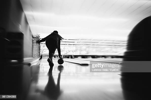 Rear View Of Woman Bowling In Alley